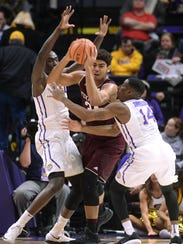 Texas A&M center Tyler Davis (34) gets caught between LSU forward Duop Reath, left, and guard Randy Onwuasor (14) during an NCAA college basketball game Tuesday, Jan. 23, 2018, in Baton Rouge, La. (Hilary Scheinuk/The Advocate via AP)