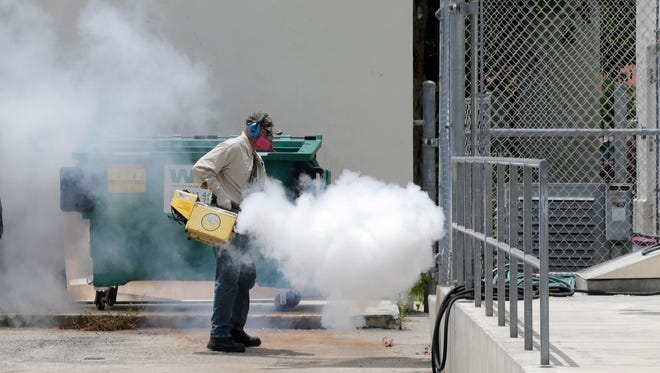 A Miami-Dade County mosquito control worker sprays around a school in the Wynwood area of Miami on Aug. 1, 2016.