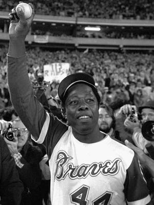 Hank Aaron holds aloft the ball he hit for his 715th home run in Atlanta's Fulton County Stadium on April 8, 1974.