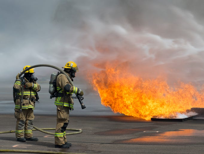 Phoenix Fire Department firefighters wait for the foam truck to extinguish the flames before entering the fuselage for a rescue during airport disaster training on Tuesday, March 24, 2014, at the Phoenix Fire Training Academy 2425 W. Lower Buckeye Road.