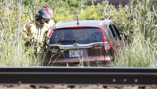 First responders check a Honda CRV that collided with a train Thursday, Aug. 18, 2016, on Lone Elm Road in the town of Black Wolf. No one was injured in the crash.