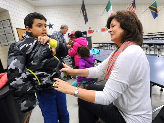 Sheryl Kendrick, right, helps Anson Cobarruvias try on a coat donated by the Big Country County Medical Society Alliance to kids at Ortiz Elementary School Monday.