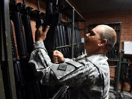Staff Sgt. Travis Osborn checks weapons in the weapons vault of the Arkansas Army National Guard's 224th Maintenance Company in Mountain Home on Wednesday.