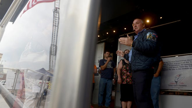 Retired FDNY firefighter Richie Murray gives a tour of the 'Never Forget' 9/11 Mobile Exhibit on Tuesday in Huntingdon.