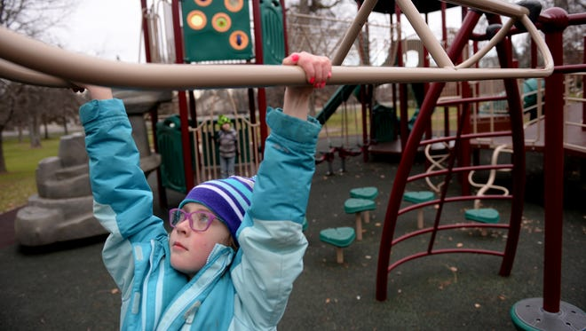 Hanna Hutchinson, 8, plays on the playground at Patriarche Park in East Lansing on Monday, Jan. 2, 2017.