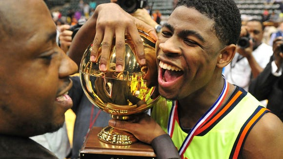 Callaway's Malik Newman celebrates with the trophy following the Chargers' win over Vicksburg in the MHSAA 5A Final.