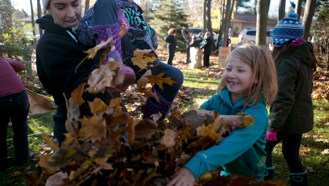 Amy Kloos of Rozellville, left, uses her daughter Maddie, 6, center, to push down leaves as Myah Slade, 6, right, adds more to the bag while they helped rake leaves at Roberta Zorman's house on East 26th Street for Make A Difference Day in Marshfield, Saturday, Oct. 25, 2014.