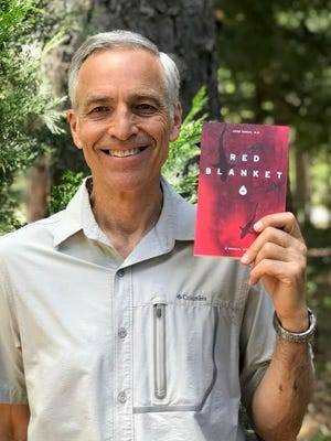 """Retired surgeon Dr. John Harch holds a copy of his new book, """"Red Blanket,"""" which recounts the his harrowing surgical training at an inner-city hospital in the Los Angeles area in the 1980s."""