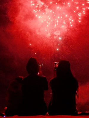 Spectators watch and record fireworks.