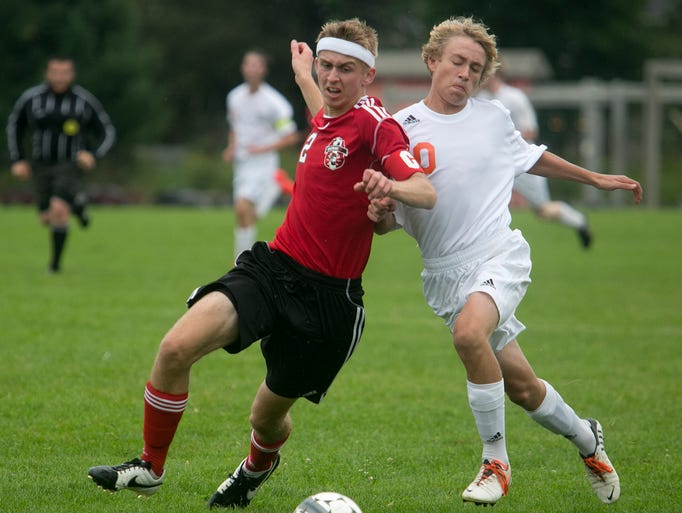 Wausau East's Tanner Frahm, left, and Marshfield's Luke McCann tangle up while going after the ball during the Wisconsin Valley Conference soccer game at Griese Park in Marshfield, Thursday, Aug. 28, 2014.