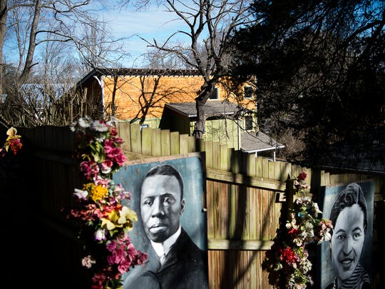 Newer homes are seen over the fence decorated with flowers and photos of historic black figures, enclosing the Burton Street Community Peace Gardens, a youth arts and education center.