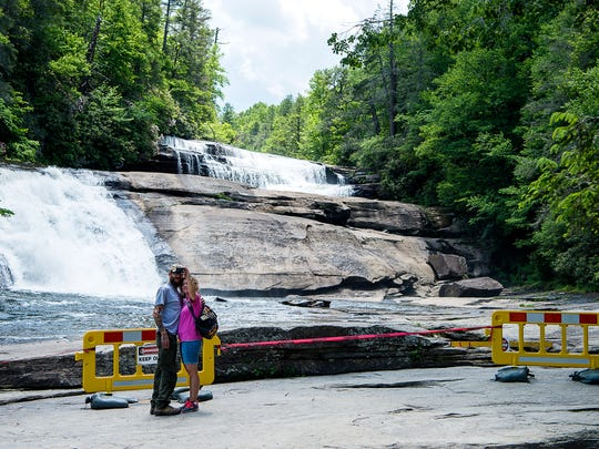 Crystal and Phillip Torbett, tourists from Virginia, pause to take a selfie in front of Triple Falls at DuPont State Forest Friday June 2, 2017.