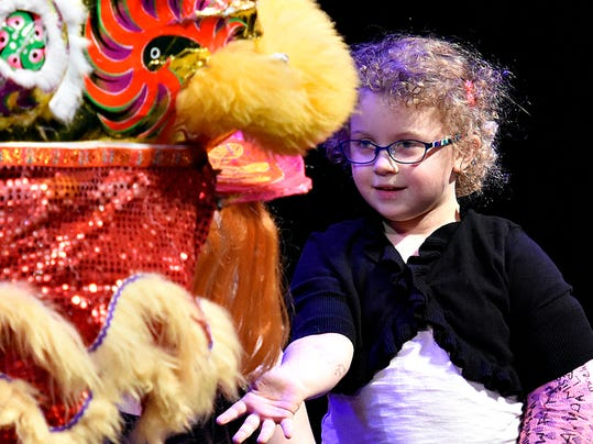 Audience participant Rosie Gray, 5, of Spring Garden Township, feeds the lion two lettuce leaves, which are then spat out as Wong People's Kung Fu School, Washington D.C.'s premier Lion Dance Team, performs the Chinese Lion Dance at the Pullo Family Performing Arts Center in York, Pa., as part of Penn State York's cultural series, on Wednesday, Oct. 14, 2015.  Dawn J. Sagert - dsagert@yorkdispatch.com