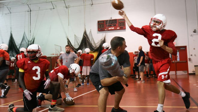 """Smyrna High quarterback Nolan Henderson throws while being """"pressured"""" by assistant coach Michael Marks during practice in the school gym Thursday."""