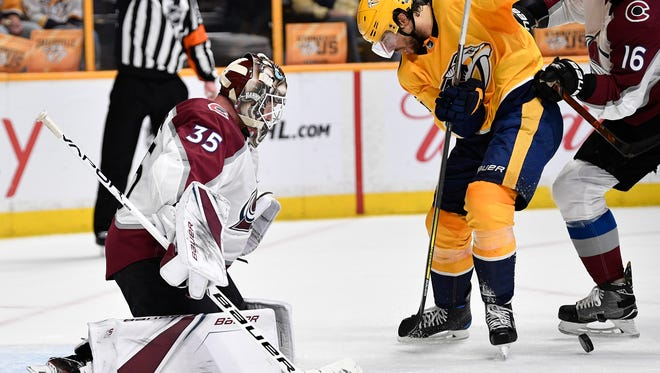 Predators Craig Smith, 15, moves the puck toward Avalanche goalie Andrew Hammond, 35, in Game 5 of the first round NHL Stanley Cup Playoffs at the Bridgestone Arena Friday, April 20, 2018, in Nashville, Tenn.