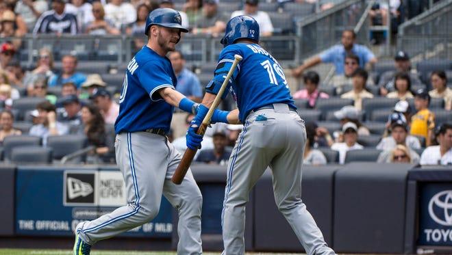 Blue Jays right fielder Jose Bautista, right, congratulates Josh Donaldson after hitting a home run.
