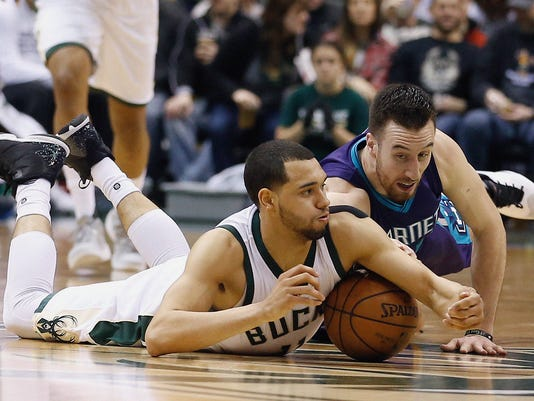 Charlotte Hornets' Frank Kaminsky III and Milwaukee Bucks' Tyler Ennis go after a loose ball during the second half of an NBA basketball game Saturday, March 26, 2016, in Milwaukee. (AP Photo/Morry Gash)