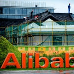 In this Monday, Sept. 15, 2014 photo, workers renovate an ancient-style building at the headquarters of Alibaba Group in Hangzhou in east China's Zhejiang province.