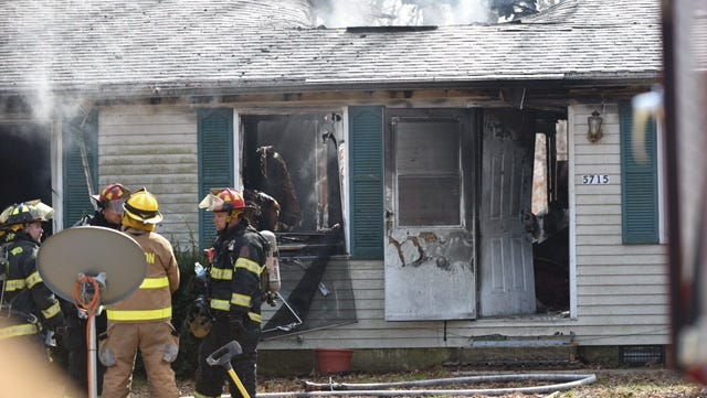 Firefighters gather outside a home in Lawrence Township ravaged by a Thursday blaze.