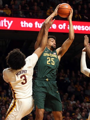 Michigan State's Kenny Goins pulls in a rebound over Minnesota's Jordan Murphy during the first half Tuesday, Feb. 13, 2018 in Minneapolis.
