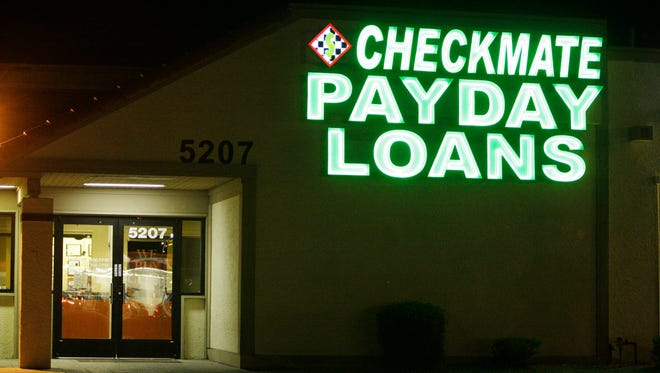 Neon signs illuminate a payday loan business in Phoenix on April 6, 2010.