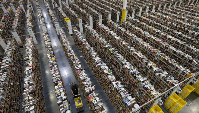 An Amazon employee walks down one of the miles of aisles at the company's fulfillment center in Phoenix, Ariz.