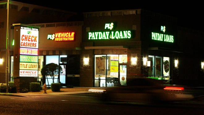 File photo taken in 2010 shows neon signs illuminating a payday loan business in Phoenix.