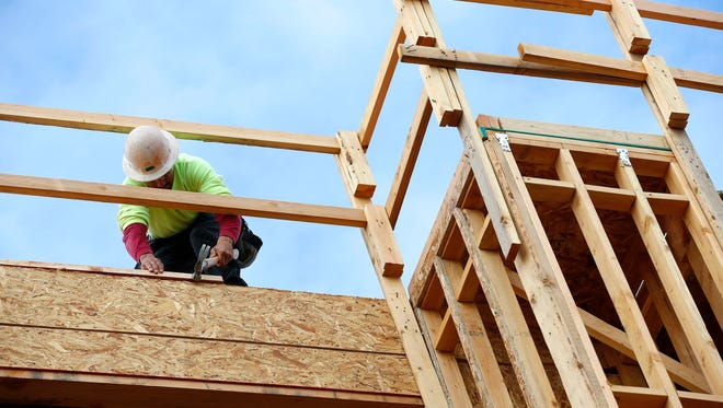 A builder works on a new apartment building under construction in this 2015 file photo.