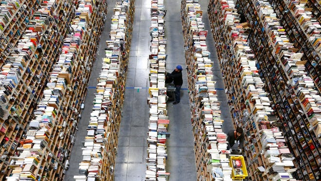 """In this Dec. 2, 2013, file photo, Amazon.com employees work the shelves along the miles of aisles at an Amazon.com Fulfillment Center on """"Cyber Monday"""", the Monday after Thanksgiving and the busiest online shopping day of the holiday season, in Phoenix. Millions of Americans are expected to log on and keep shopping on Monday, Dec. 1, 2014, the day dubbed Cyber Monday. (AP Photo/Ross D. Franklin, File)"""