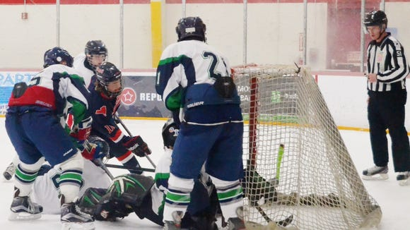 Byram Hills freshman Ethan Behar keeps digging for the puck and eventually scores in the Bobcats' 4-3 win over Mount Pleasant on Saturday at Westchester Skating Academy