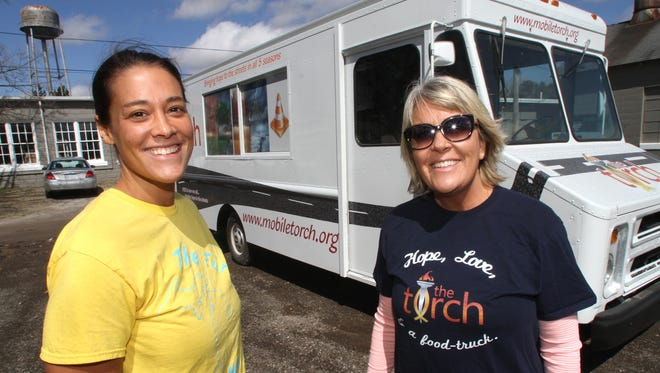 Sarah Ruddle, left, and Rhonda Callanan pose by their food truck The Torch in this 2015 photograph.