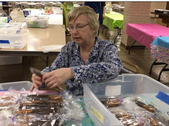 St. Peter's volunteer Linda Spicer arranges chocolate covered treats Monday for the annual bake sale which will be held Tuesday and Wednesday in the St. Peter's Church basement.
