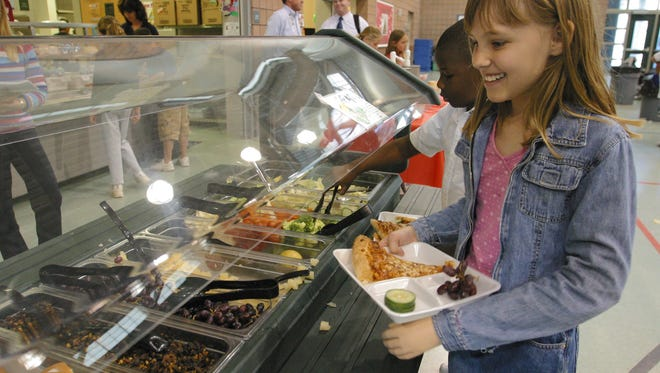 Students receive lunch at a school cafeteria