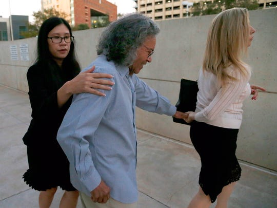 Billionaire founder of Insys Therapeutics John Kapoor, center, is escorted out of U.S. District Court after being arrested earlier Thursday, Oct. 26, 2017, in Phoenix. Kapoor and other defendants in the fraud and racketeering case are accused of offering bribes to doctors to write large numbers of prescriptions for a fentanyl-based pain medication meant only for cancer patients with severe pain. A judge set bail at $1 million for Kapoor, saying he must wear electronic monitoring and surrender his passports.