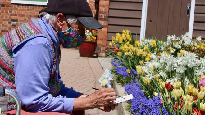 Kathy VanTubbergen wears a mask while painting watercolors of the tulips and flowers on May 6 at Windmill Island in Holland. On Tuesday, July 28, the Ottawa County board of commissioners voted unanimously to extend a local state of emergency in place due to the coronavirus pandemic.