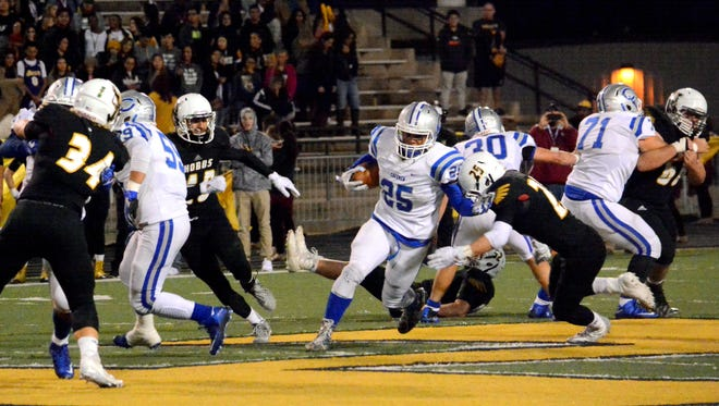 Carlsbad's Dominic Rodriguez fights for extra yards in the first quarter Friday.
