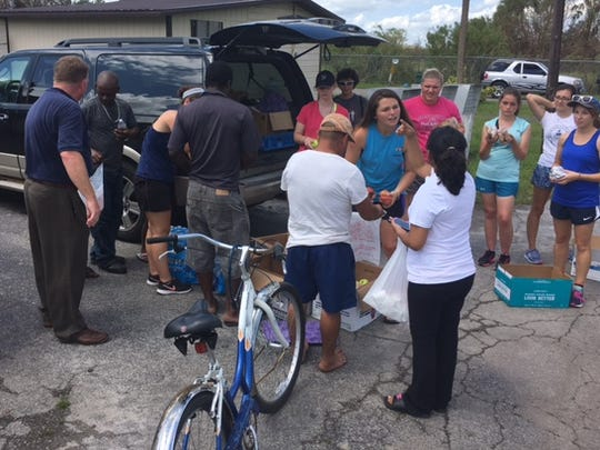 Students and staff from Ave Maria University pass out food and water to residents of Immokalee on Wednesday.