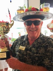 Yacht Club member Geoff Walker shows off the Derby Day Trophy he received for the Most Humorous Kentucky Derby hat. His hat featured mint juleps sitting on a rose-covered silver serving tray.
