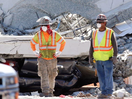 Workers stand in front of crushed cars under a section of a collapsed pedestrian bridge, Friday, March 16, 2018, near Florida International University in the Miami area. The new pedestrian bridge that was under construction collapsed onto a busy Miami highway Thursday afternoon, crushing vehicles beneath massive slabs of concrete and steel, killing and injuring several people, authorities said.