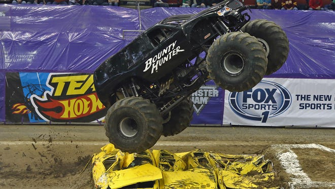 Driver Darren Migues, in Bounty Hunter, bounces over cars during the Monster Jam competition held at Wells Fargo Arena in Des Moines on Jan. 4, 2014.