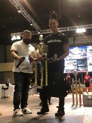 January Fonseca Sabune, a Montclair barber, participates in hair cutting and styling competitions against other female barbers. Fonseca-Sabune, right, receives a trophy for winning second place in the Connecticut Barber Expo on April 22, 2018, at the Connecticut Convention Center in Hartford, Conn.
