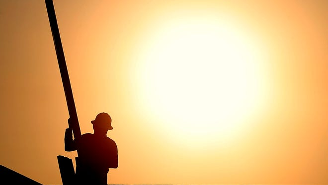 A construction worker is shown atop a roof at sunrise to beat daytime high temperatures, Thursday, June 27, 2013 in Queen Creek, Ariz.  Another heat wave is forecast for this weekend.