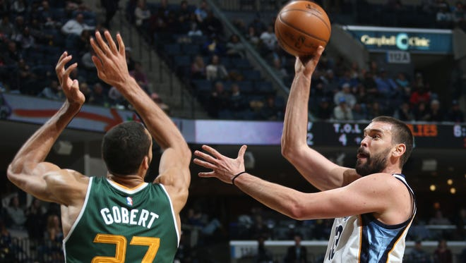 Memphis Grizzlies center Marc Gasol (right) shoots over the defense of Utah Jazz Rudy Gobert.