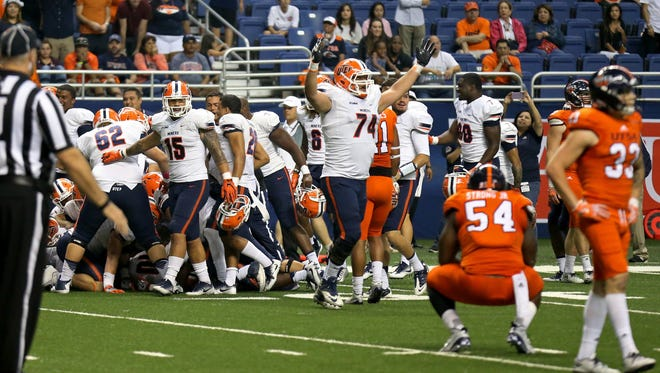 Members of the UTEP (white) celebrate after defeating the UTSA in five overtimes in an NCAA college football game in San Antonio on Saturday, Oct. 22, 2016. UTEP won 52-49. (Edward A. Ornelas/The San Antonio Express-News via AP)
