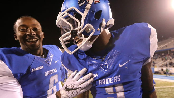 MTSU's Houston Brown (6) and Jeremy Cutrer celebrate the school's victory over Marshall in a triple overtime game, on Saturday, Nov. 7, 2015, in Murfreesboro, Tenn.