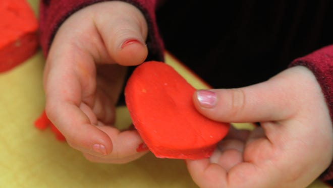 A preschooler holds a heart she made of clay for Valentine's Day.
