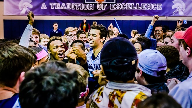 Westin Myles ,center, of East Lansing is swarmed by East Lansing Students after the Trojans' overtime Class A district final defeat of Grand Ledge Friday March 11, 2016 at East Lansing High.  KEVIN W. FOWLER PHOTO