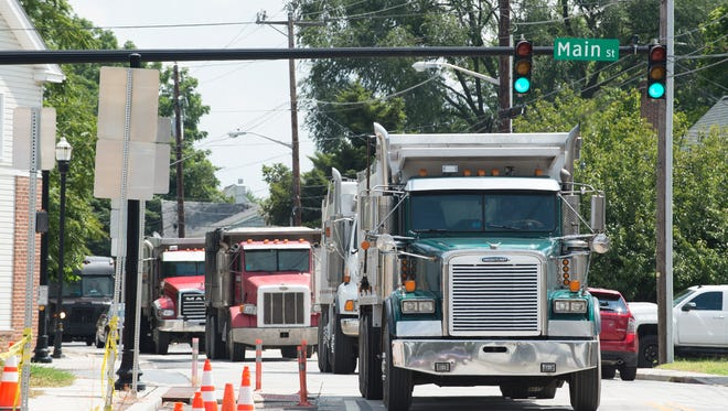 A line of dump truck travels on West Camden-Wyoming Avenue in Camden.