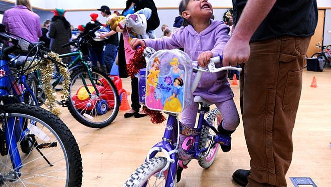 Giselle Gonzalez, 4, looks up at volunteer Steve Hanks as she tries out her new bike in this 2011 file photo during Realities for Children's annual Bikes for Tykes event held at First Presbyterian Church in Fort Collins.