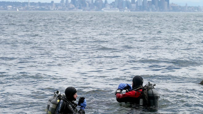North Kitsap School District Superintendent Laurynn Evans, left, is an avid scuba diver who has taken underwater video for film companies. She is also an expert cave diver. She is getting ready to go under the water at Rockaway Beach on Bainbridge Island, with her husband and diving partner Rob Bugles.